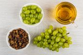 Small Bowls With Berries Of Grape And Raisins, Cup With Grape Juice, Bunch Of Grapes On Wooden Table poster