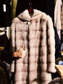 Male Hand Holds Fur Coat In Luxury Shop Showing Thumbs Up. Furry Coat In Beige Color In Mans Hand. B poster