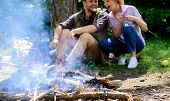Camping Activity. Couple In Love Camping Forest Eating Roasted Marshmallows. Couple Eat Roasted Mars poster