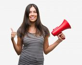 Young hispanic woman holding megaphone happy with big smile doing ok sign, thumb up with fingers, ex poster