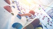 Young Boy Is Climbing On Artificial Climbing Wall poster