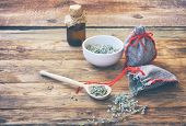 Homemade Sachets With Wormwood, White Bowl With Dry Herb, Bottle Of Oil On Wooden Table Closeup poster
