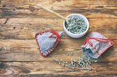 Homemade Sachets With Wormwood, White Bowl With Dry Herbs On Wooden Table, Top View poster