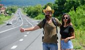 Travellers Try To Stop Car. Hitchhiking Is One Of Cheapest Ways Of Traveling. Couple Hitchhikers Tra poster