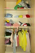 Colorful Clothes In The Closet. Cleaning Concept. Scattered Clothes In The Closet. Clothes In Dressi poster