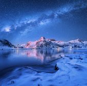 Milky Way Above Frozen Sea Coast And Snow Covered Mountains In Winter At Night In Lofoten Islands, N poster