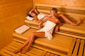 stock photo of sauna  - Sauna two healthy beautiful women relaxing lying wrapped in towel - JPG
