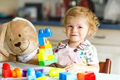 Adorable Toddler Girl With Favorite Plush Bunny Playing With Educational Toys In Nursery. Happy Heal poster