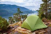 Camping tent at scenic wild campsite on a lake shore with mountain range in background - camping in  poster