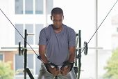 Black Man Exercising Pecs On Gym Equipment. Young Guy Wearing T-shirt And Standing With Window In Ba poster