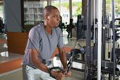 Focused Black Man Exercising Pecs On Gym Equipment. Young Guy Wearing T-shirt And Standing. Bodybuil poster