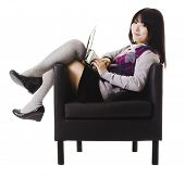 stock photo of knee-high socks  - Chinese student working on a laptop while sitting in a leather chair - JPG