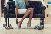 Closeup Of Young Woman Trying On Shoes In Store. Beautiful Black Girl Choosing Shoes To Buy In Bouti poster