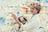 Mature Female Pharmacist At Work In Farmacy Store. Adult Pharmacist Wearing White Coat Holding Table poster