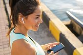 Tired Fitness Woman Sweating Taking A Break Listening To Music On Phone After Difficult Training. poster