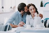 Young Couple Drinking Coffee Together At Home. Handsome Man Hugging And Kissing Beautiful Woman Sitt poster