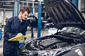 Auto Car Repair Service Center. Mechanic Examining Car Engine poster