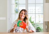 Young woman at home holding flag of Portugal with a happy face standing and smiling with a confident poster
