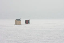 image of ice fishing  - A pair of ice fishing houses on a frozen lake in the morning fog - JPG