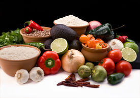 picture of mexican food  - attractive display of all of the fresh ingredients peppers onions tomatos avacados rice and beans for creating traditional mexican cruisine on a black background white foreground - JPG