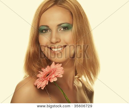 Beautiful young woman with gerber flower.Warm yellow tones.
