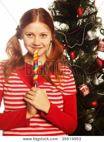 Pretty young redhair woman  holding lolly pop. Christmas tree.