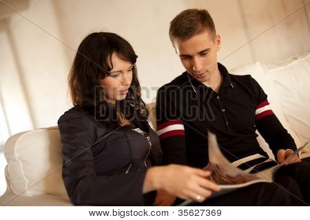 Lovely couple reading a book together on the sofa at home