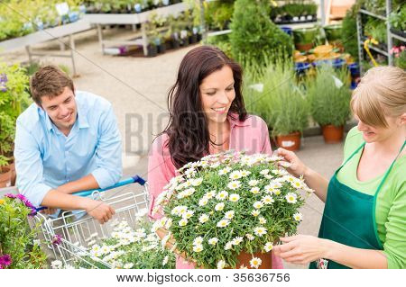Florist assisting young woman choose flowers at garden shopping center