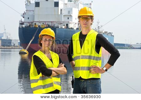 Two dockers, a man and a woman, posing in front of a huge cargo ship, moored off at an anchor buoy in an industrial harbor