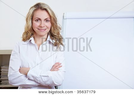 Happy blonde business woman standing in front of a flipchart