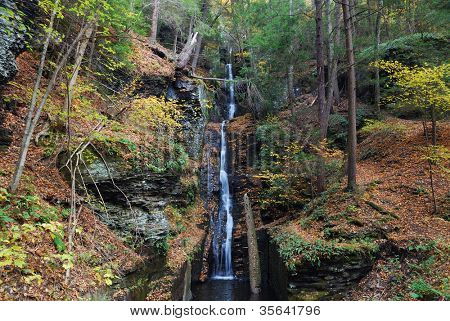 Autumn Waterfall in mountain with foliage and woods over rocks. Silver Thread Falls from Dingmans Falls Pennsylvania.