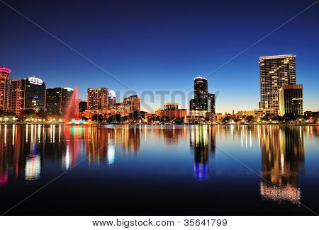 Orlando downtown skyline panorama over Lake Eola at night with urban skyscrapers and clear sky.