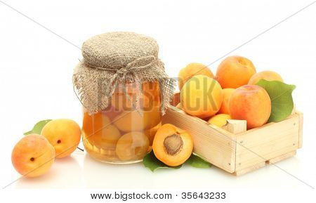 canned apricots in a jar and fresh apricots in wooden box isolated on white