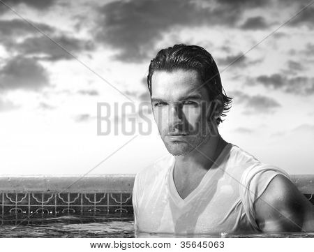 Hot sexy guy in wet tee shirt in swimming pool with beautiful skyscape behind