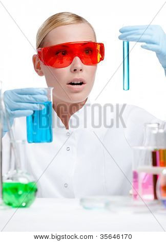 Wondered female doctor in spectacles does some experiments, isolated on white