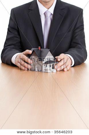 Conceito imóveis - empresário as mãos em torno do modelo de arquitetura casa