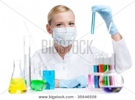 Female chemist in respirator holds a vial with blue liquid, isolated on white
