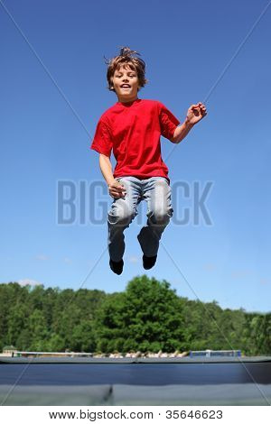 Joyful boy dressed in red T-shirt jumps on trampoline at sunny summer day