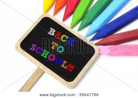 sentence back to school written in a blackboard label and some crayons of different colors in the background