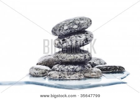 a pile of balanced zen stones covered with water on a white background