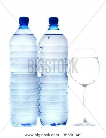 Bottles of mineral water with a glass. Isolated.