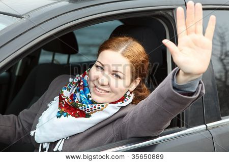 Pretty Young Caucasian Woman Waving Hers Hand Sitting In Car