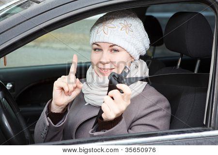 Young Woman Sitting In Car And Holding Seat Belt In Hand
