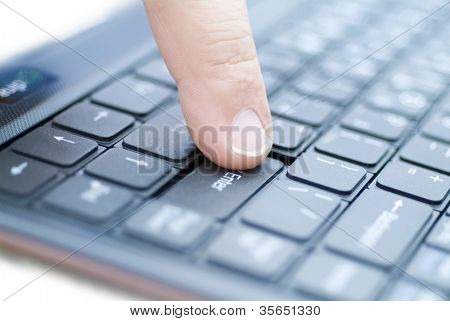 man finger on the enter key. Small DOF