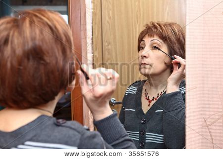 Mature Caucasian Woman Applying Make Up Against Mirror In Domestic Room