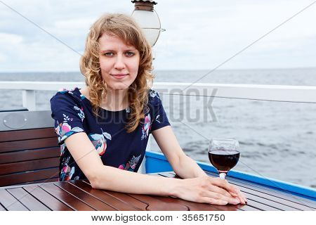 Serene Woman In Dress With Wine Glass Sitting At The Table