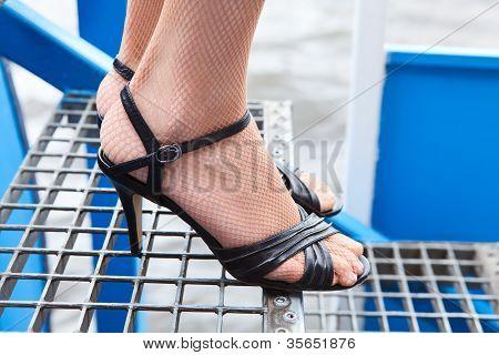 weibliche Beine in Fischnetz-Strumpfhose und Schuhe in Stöckelschuhen stehen auf Treppen