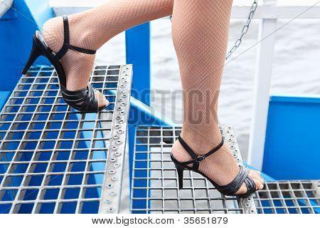 weibliche Beine in Fischnetz-Strumpfhose und Schuhe in Stöckelschuhen gehen auf Treppen