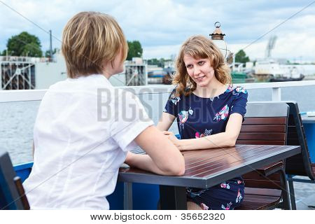 Two Frendly Talking Girlfriends At Cafe Table