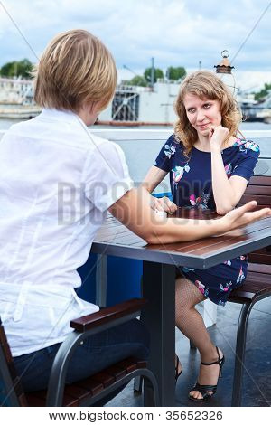 Frendly Speaking Two Girlfriends At Cafe Table
